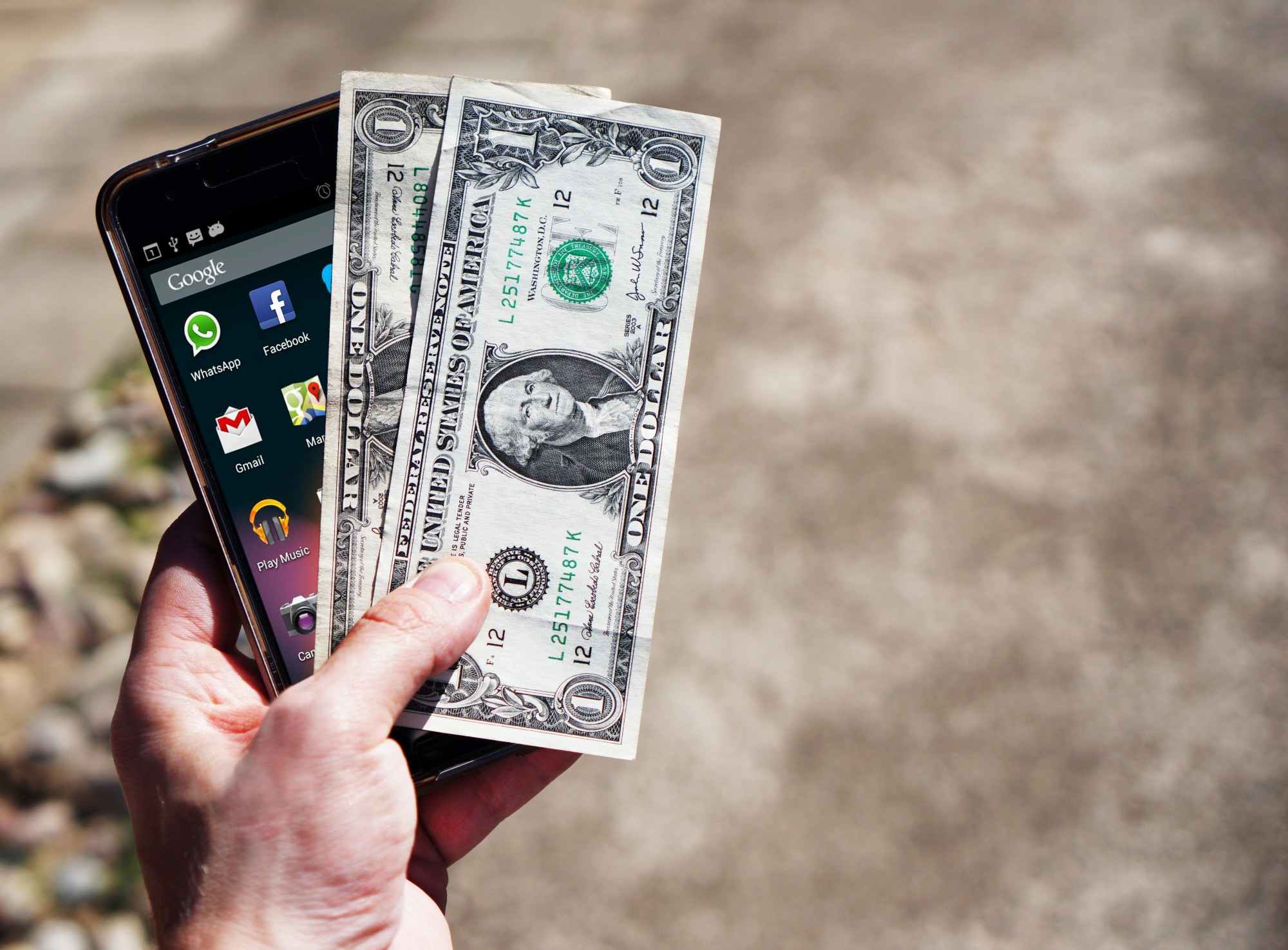 smart phone and cash in person's hand